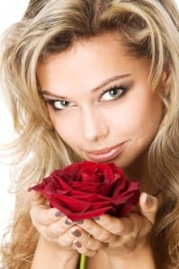 Beautiful young blond woman holding a red rose