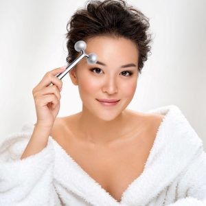 women holding face roller facial massager metal